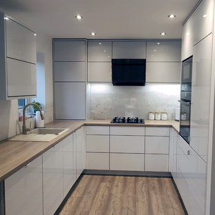 This is an example of a medium sized modern u-shaped enclosed kitchen in Other with an integrated sink, flat-panel cabinets, white cabinets, laminate countertops, black appliances, laminate floors, no island, brown floors and brown worktops.