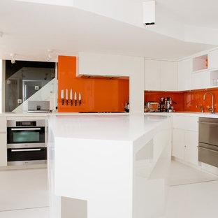 Diseño de cocina comedor en L, actual, de tamaño medio, con fregadero bajoencimera, armarios con paneles lisos, puertas de armario blancas, salpicadero naranja, salpicadero de vidrio templado, electrodomésticos de acero inoxidable, una isla y encimera de acrílico