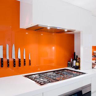 Mittelgroße Moderne Wohnküche in L-Form mit Unterbauwaschbecken, flächenbündigen Schrankfronten, weißen Schränken, Mineralwerkstoff-Arbeitsplatte, Küchenrückwand in Orange, Glasrückwand, Küchengeräten aus Edelstahl und Kücheninsel in London