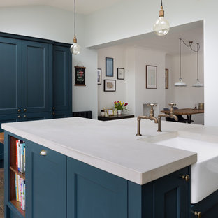 Inspiration for a medium sized traditional kitchen/diner in Other with a belfast sink, shaker cabinets, blue cabinets, concrete worktops, black appliances, porcelain flooring, an island and brown floors.
