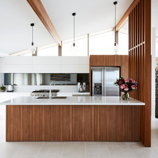 Photo of a mid-sized contemporary galley open plan kitchen in Sydney with a double-bowl sink, flat-panel cabinets, white cabinets, quartz benchtops, grey splashback, mirror splashback, stainless steel appliances, ceramic floors, with island, grey floor and white benchtop.