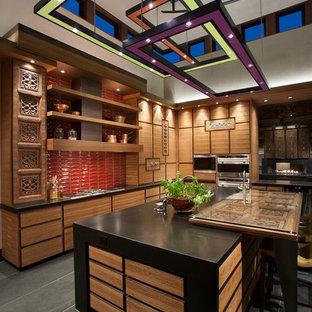 フェニックスの大きいサンタフェスタイルのおしゃれなキッチン (ドロップインシンク、フラットパネル扉のキャビネット、中間色木目調キャビネット、オニキスカウンター、赤いキッチンパネル、モザイクタイルのキッチンパネル、パネルと同色の調理設備、スレートの床、黒い床) の写真