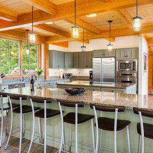 Immagine di una grande cucina american style con lavello sottopiano, ante in stile shaker, ante verdi, top in granito, elettrodomestici in acciaio inossidabile, pavimento in ardesia, 2 o più isole, pavimento grigio e travi a vista