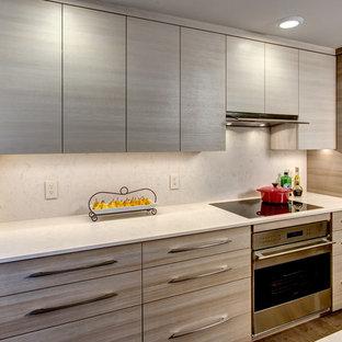 Idee per una piccola cucina design con lavello sottopiano, ante lisce, ante marroni, top in quarzo composito, paraspruzzi beige, elettrodomestici in acciaio inossidabile, pavimento in sughero e penisola