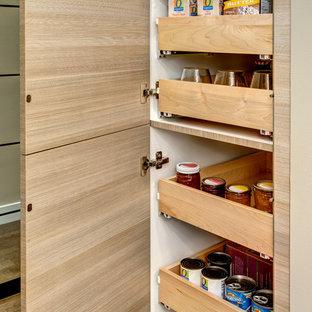 Inredning av ett modernt litet kök, med en undermonterad diskho, släta luckor, bänkskiva i kvarts, beige stänkskydd, rostfria vitvaror, korkgolv och en halv köksö