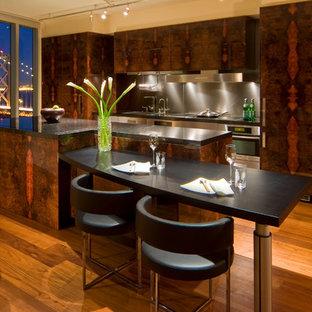 サンフランシスコの中サイズのモダンスタイルのおしゃれなキッチン (パネルと同色の調理設備、アンダーカウンターシンク、フラットパネル扉のキャビネット、無垢フローリング、濃色木目調キャビネット、ステンレスカウンター、茶色い床) の写真