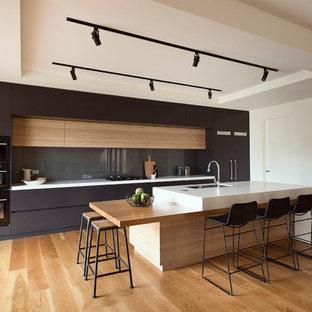 Zweizeilige, Mittelgroße Moderne Küche mit Unterbauwaschbecken, flächenbündigen Schrankfronten, Küchenrückwand in Grau, Glasrückwand, schwarzen Elektrogeräten, braunem Holzboden, Kücheninsel, schwarzen Schränken und weißer Arbeitsplatte in Melbourne