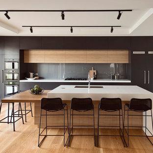 Идея дизайна: большая параллельная кухня в стиле модернизм с обеденным столом, врезной раковиной, плоскими фасадами, черными фасадами, фартуком из стекла, черной техникой, островом и паркетным полом среднего тона