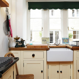 Photo of a small classic l-shaped kitchen/diner in London with a belfast sink, raised-panel cabinets, wood worktops, no island, brown worktops and beige cabinets.