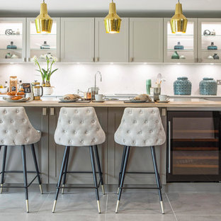 Medium sized classic l-shaped kitchen in Surrey with grey cabinets, white splashback, stainless steel appliances, an island, grey floors, glass-front cabinets, wood worktops and beige worktops.