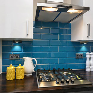 Small contemporary galley separate kitchen in London with an integrated sink, flat-panel cabinets, white cabinets, wood benchtops, blue splashback, ceramic splashback, stainless steel appliances, ceramic floors and no island.