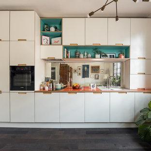 Пример оригинального дизайна: маленькая линейная кухня-гостиная в стиле фьюжн с плоскими фасадами, белыми фасадами, столешницей из ламината, фартуком из зеркальной плитки, темным паркетным полом, накладной раковиной, черной техникой, черным полом и оранжевой столешницей без острова