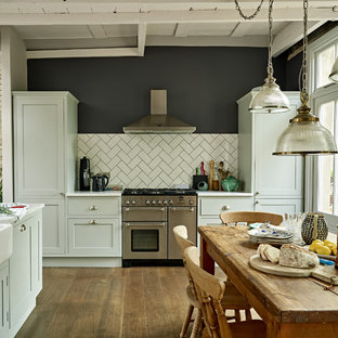 Inspiration for a large scandinavian u-shaped eat-in kitchen in London with a farmhouse sink, green cabinets, marble benchtops, medium hardwood floors, brown floor, white benchtop, shaker cabinets, white splashback, subway tile splashback and stainless steel appliances.
