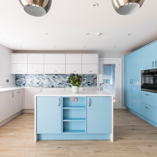 This is an example of a beach style kitchen in Dorset with a submerged sink, flat-panel cabinets, blue cabinets, multi-coloured splashback, stainless steel appliances, an island, beige floors and white worktops.
