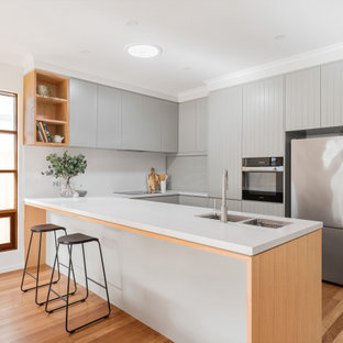 This is an example of a contemporary u-shaped kitchen in Adelaide with an undermount sink, flat-panel cabinets, grey cabinets, white splashback, stainless steel appliances, medium hardwood floors, a peninsula, brown floor and white benchtop.