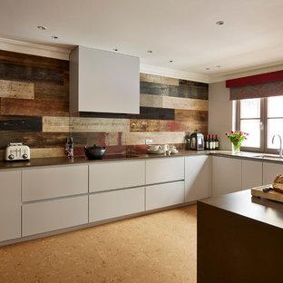 Inspiration pour une cuisine américaine design avec un placard à porte plane, des portes de placard grises, un plan de travail en quartz, un sol en liège et un îlot central.