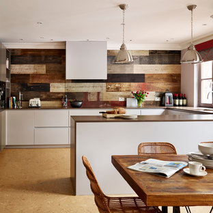 Inspiration for a medium sized contemporary u-shaped kitchen/diner in London with grey cabinets, quartz worktops, cork flooring, an island, a submerged sink, flat-panel cabinets, brown splashback and black appliances.