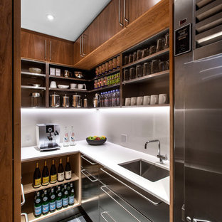 Design ideas for a contemporary u-shaped kitchen pantry in Toronto with a submerged sink, flat-panel cabinets, stainless steel cabinets, stainless steel appliances, no island and grey floors.