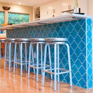 Foto di una cucina minimal di medie dimensioni con lavello stile country, ante lisce, ante bianche, top in quarzite, paraspruzzi blu, paraspruzzi con piastrelle in ceramica, elettrodomestici in acciaio inossidabile, parquet chiaro e isola