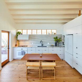 Ispirazione per una cucina contemporanea con lavello sottopiano, ante lisce, ante bianche, paraspruzzi bianco, elettrodomestici bianchi, pavimento in legno massello medio, nessuna isola, pavimento marrone e top bianco