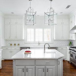 Idéer för avskilda, mellanstora vintage vitt kök, med en undermonterad diskho, luckor med upphöjd panel, vita skåp, bänkskiva i kvarts, vitt stänkskydd, rostfria vitvaror, mellanmörkt trägolv, en köksö, brunt golv och stänkskydd i tunnelbanekakel