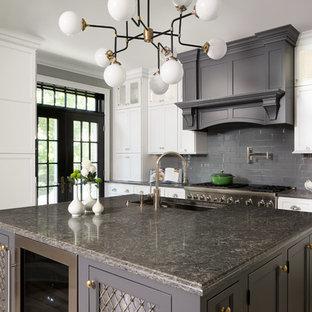 Пример оригинального дизайна интерьера: угловая кухня-гостиная среднего размера в классическом стиле с врезной раковиной, фасадами с утопленной филенкой, белыми фасадами, серым фартуком, фартуком из плитки кабанчик, островом, столешницей из гранита, техникой под мебельный фасад, паркетным полом среднего тона и бежевым полом