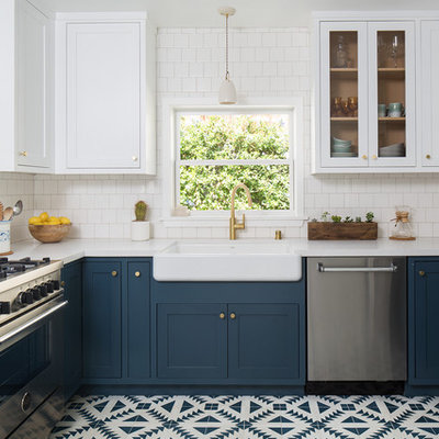 Inspiration for a mid-sized craftsman u-shaped cement tile floor and blue floor enclosed kitchen remodel in Los Angeles with a farmhouse sink, shaker cabinets, blue cabinets, quartz countertops, white backsplash, ceramic backsplash, stainless steel appliances and no island