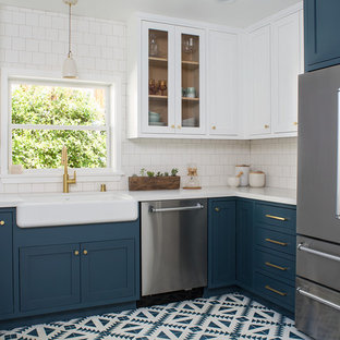 Photo of a mid-sized arts and crafts u-shaped separate kitchen in Los Angeles with a farmhouse sink, shaker cabinets, blue cabinets, quartz benchtops, white splashback, ceramic splashback, stainless steel appliances, cement tiles, no island and blue floor.