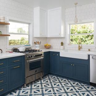 ロサンゼルスの中サイズのトランジショナルスタイルのおしゃれなコの字型キッチン (エプロンフロントシンク、シェーカースタイル扉のキャビネット、青いキャビネット、クオーツストーンカウンター、白いキッチンパネル、セラミックタイルのキッチンパネル、シルバーの調理設備の、セメントタイルの床、アイランドなし、青い床) の写真