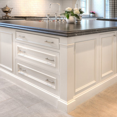 Example of a large transitional u-shaped eat-in kitchen design in Chicago with a farmhouse sink, recessed-panel cabinets, white cabinets, white backsplash, stainless steel appliances and two islands