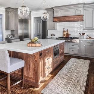 Huge traditional enclosed kitchen inspiration - Example of a huge classic dark wood floor and brown floor enclosed kitchen design in Dallas with shaker cabinets, gray cabinets, white backsplash, subway tile backsplash, stainless steel appliances, an island and white countertops