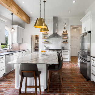 Large u-shaped eat-in kitchen in New Orleans with an undermount sink, recessed-panel cabinets, white cabinets, quartzite benchtops, white splashback, subway tile splashback, stainless steel appliances, brick floors, with island, brown floor and grey benchtop.