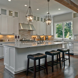 Large traditional open concept kitchen remodeling - Example of a large classic l-shaped dark wood floor open concept kitchen design in Atlanta with a farmhouse sink, shaker cabinets, white cabinets, marble countertops, gray backsplash, stainless steel appliances, an island and white countertops