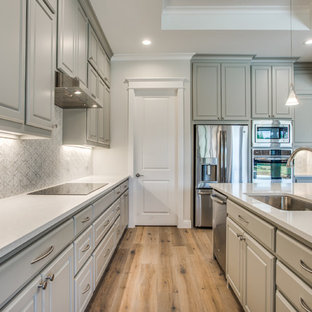 Design ideas for a large transitional l-shaped open plan kitchen in Dallas with an undermount sink, raised-panel cabinets, grey cabinets, stainless steel appliances, plywood floors and with island.
