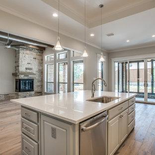 Offene, Große Klassische Küche in L-Form mit Unterbauwaschbecken, profilierten Schrankfronten, grauen Schränken, Küchengeräten aus Edelstahl, Sperrholzboden und Kücheninsel in Dallas