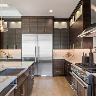 Contemporary l-shaped kitchen in Boise with a farmhouse sink, flat-panel cabinets, red cabinets, white splashback, stainless steel appliances, light hardwood floors, with island, beige floor and white benchtop.
