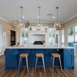 Transitional kitchen in Brisbane with a farmhouse sink, shaker cabinets, blue cabinets, white splashback, black appliances, medium hardwood floors, with island, brown floor and grey benchtop.