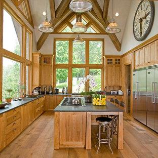ニューヨークの巨大なラスティックスタイルのおしゃれなキッチン (アンダーカウンターシンク、シェーカースタイル扉のキャビネット、中間色木目調キャビネット、シルバーの調理設備、無垢フローリング、オニキスカウンター) の写真