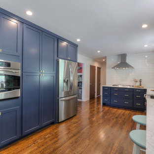 This is an example of a midcentury galley eat-in kitchen in Nashville with a farmhouse sink, shaker cabinets, blue cabinets, marble benchtops, white splashback, ceramic splashback, stainless steel appliances, medium hardwood floors and no island.