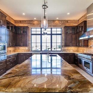オースティンの大きいラスティックスタイルのおしゃれなキッチン (アンダーカウンターシンク、シェーカースタイル扉のキャビネット、中間色木目調キャビネット、御影石カウンター、茶色いキッチンパネル、磁器タイルのキッチンパネル、シルバーの調理設備の、トラバーチンの床) の写真