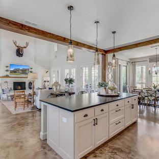 Zweizeilige, Mittelgroße Landhaus Wohnküche mit Landhausspüle, Schrankfronten im Shaker-Stil, grauen Schränken, Küchenrückwand in Weiß, Betonboden, Kücheninsel und schwarzer Arbeitsplatte in Dallas