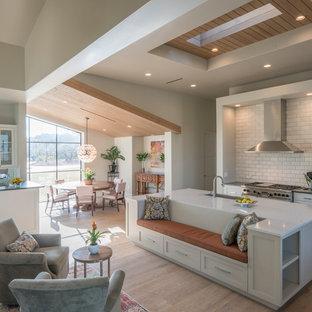 Exemple d'une cuisine ouverte tendance avec un évier 1 bac, un placard à porte shaker, des portes de placard blanches, une crédence blanche, une crédence en carrelage métro, un électroménager en acier inoxydable, un sol en bois clair, un îlot central et un sol beige.