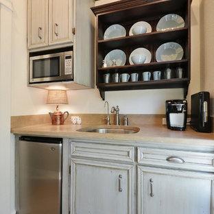 Idee per una piccola cucina parallela rustica chiusa con lavello sottopiano, ante con finitura invecchiata, top in pietra calcarea, paraspruzzi in lastra di pietra, elettrodomestici in acciaio inossidabile e pavimento in pietra calcarea