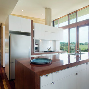 Inspiration for an expansive modern galley open plan kitchen in Melbourne with a drop-in sink, flat-panel cabinets, stainless steel appliances, wood benchtops, white cabinets, white splashback, glass sheet splashback, dark hardwood floors and with island.