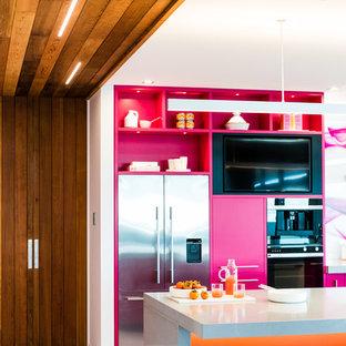 Zweizeilige, Große Moderne Küche mit Vorratsschrank, Unterbauwaschbecken, orangefarbenen Schränken, Quarzit-Arbeitsplatte, bunter Rückwand, Glasrückwand, Küchengeräten aus Edelstahl, Keramikboden, Kücheninsel, weißem Boden und grauer Arbeitsplatte in Napier-Hastings