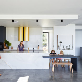 This is an example of a modern galley open plan kitchen in Gold Coast - Tweed with an undermount sink, flat-panel cabinets, light wood cabinets, white splashback, black appliances, concrete floors, with island, grey floor and white benchtop.