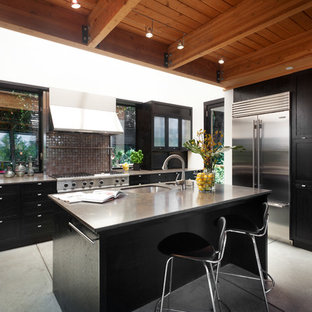 Large contemporary u-shaped eat-in kitchen in San Francisco with an undermount sink, shaker cabinets, dark wood cabinets, limestone benchtops, metallic splashback, glass tile splashback, stainless steel appliances, concrete floors, with island, grey floor and brown benchtop.