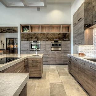 Bild på ett stort funkis u-kök, med en dubbel diskho, släta luckor, skåp i slitet trä, bänkskiva i kvartsit, vitt stänkskydd, rostfria vitvaror, klinkergolv i porslin, en köksö och grått golv