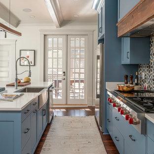 アトランタの中サイズのヴィクトリアン調のおしゃれなキッチン (一体型シンク、フラットパネル扉のキャビネット、青いキャビネット、人工大理石カウンター、マルチカラーのキッチンパネル、セラミックタイルのキッチンパネル、シルバーの調理設備の、無垢フローリング、茶色い床、白いキッチンカウンター) の写真