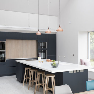 Kitchen - large contemporary single-wall concrete floor and gray floor kitchen idea in Other with an integrated sink, solid surface countertops, black appliances, an island, flat-panel cabinets and black backsplash